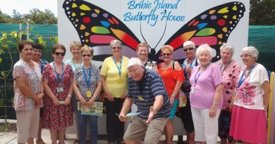 Image is of the 50+ club standing in front the Bribie Island Butterfly House.