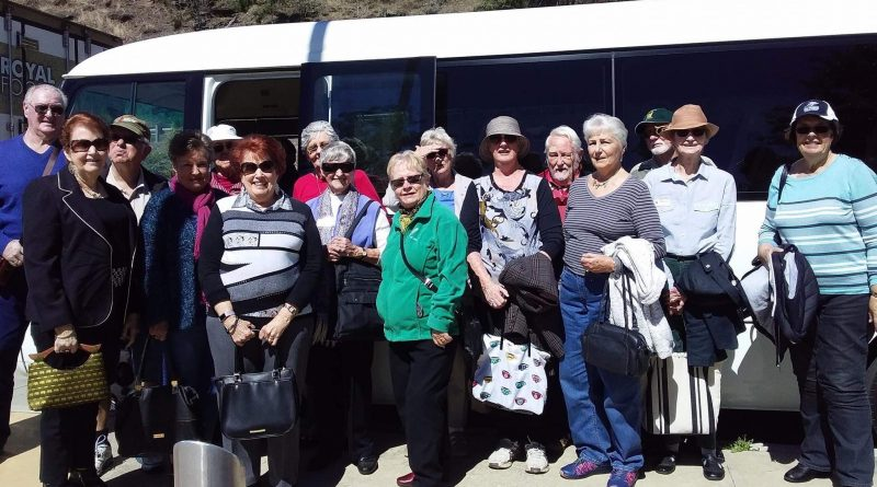 Probus club members standing in front of bus before a fun day out.