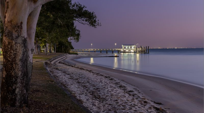 Shoreline at dusk with jetty lights.
