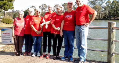Members of the Heart Foundation Forest Lake Walking Group stand together in front of the Lake.