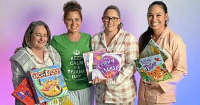 Four volunteers for Pyjama Angels wearing pyjamas and holding children's books.