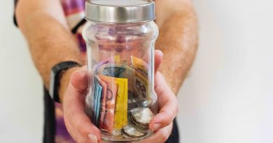 Person holding out a jar of Australian money